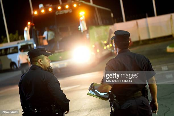 Salvadoran police officers guard a bus that transported Cuban migrants in San Luis Talpa 44 km south of San Salvador on January 13 2016 A group of...