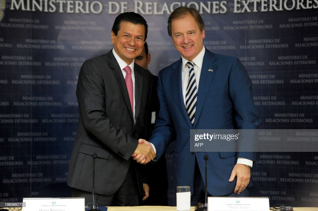 Salvadorean Foreign Affairs Minister Hugo Martinez (L) and Hugo Swire, Minister of State at the Foreign and Commonwealth Office (R) shake hands after a press conference at the Foreign Affairs ministry in San Salvador, on Novermber 14, 2012. Mr.Swire visits El Salvador for the reopening of the British embassy in the country. AFP PHOTO/ Jose CABEZAS