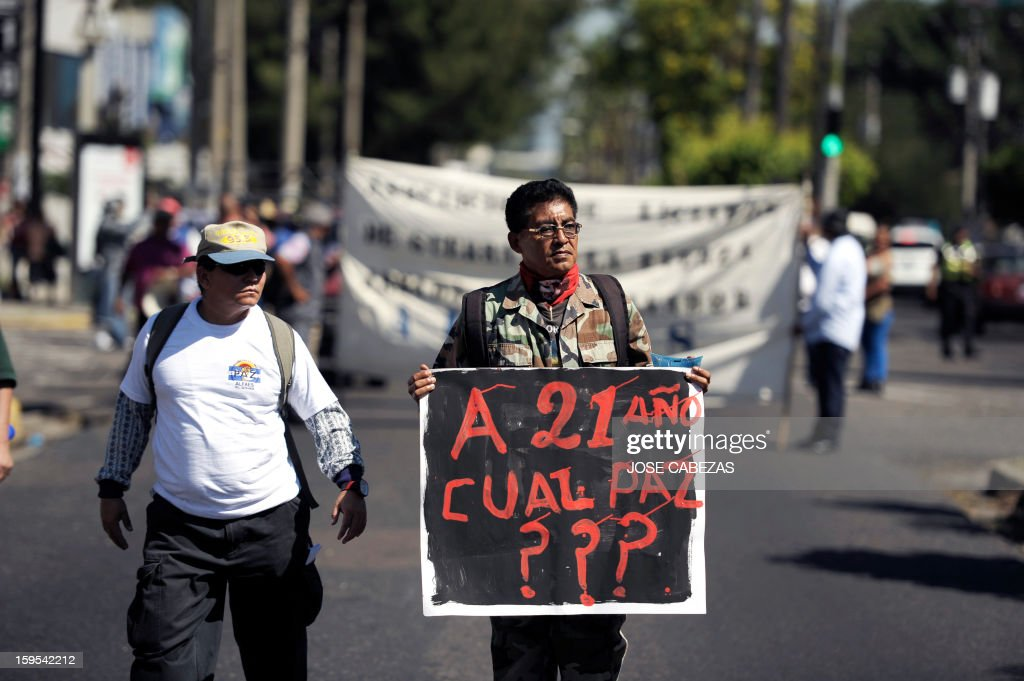 A Salvadorean veteran of the civil war (1980 to 1992) holds a sign reading '21 years later, what peace?' during a march to demand the pay of higher pensions in San Salvador, on January 15, 2013, on the 21st. anniversay of the peace agreements. AFP PHOTO/ Jose CABEZAS