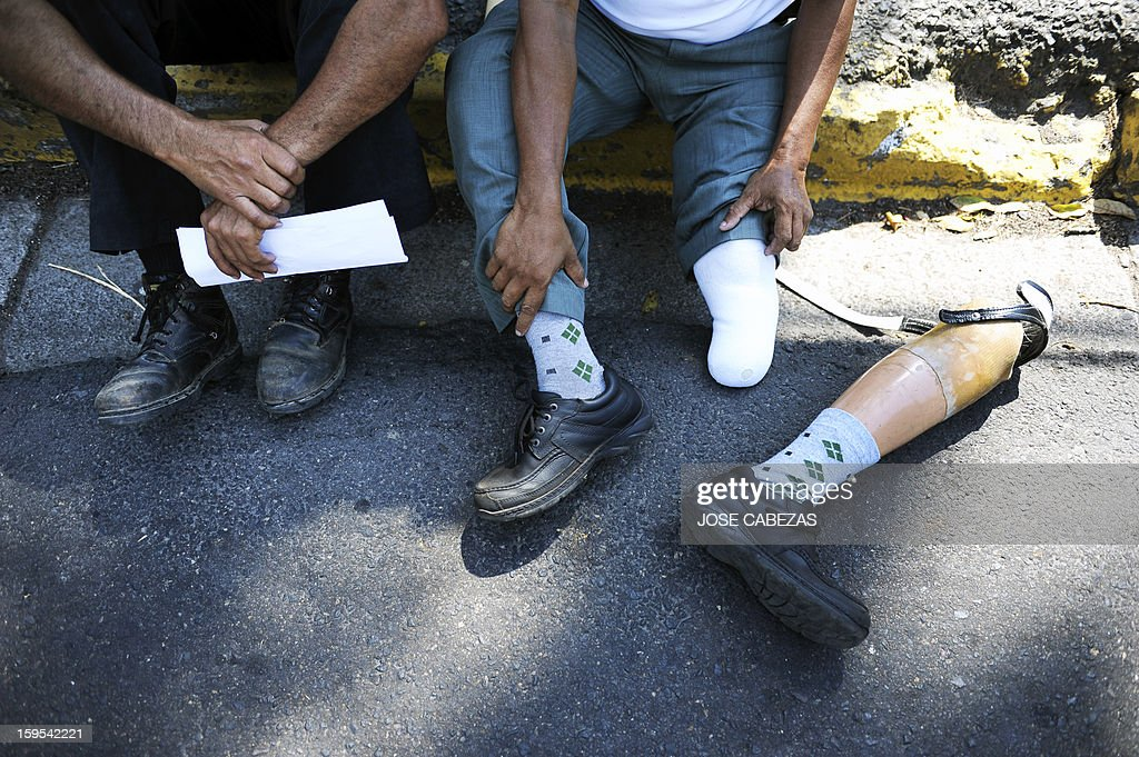Salvadorean veterans of the civil war (1980 to 1992) rest after a march near the presidential palace in San Salvador, on January 15, 2013, on the 21st. anniversay of the peace agreements. Veterans marched to demand the pay of higher pensions. AFP PHOTO/ Jose CABEZAS