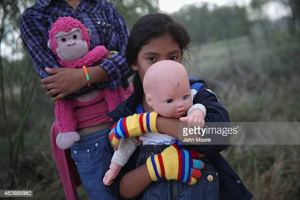 Salvadorian immigrant Stefany Marjorie holds her doll Rodrigo after crossing the Rio Grande from Mexico into the United States with her family on...