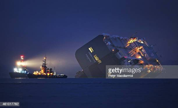 A salvage tug lights the hull of the stricken Hoegh Osaka cargo ship after it ran aground on a sand bank in the Solent on January 4 2015 in Cowes...