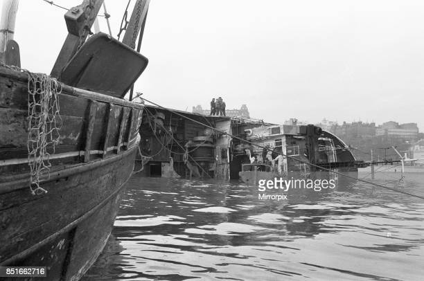 Salvage workers board the J Marr fishing trawler Navena after she was beached on Scarborough's south beach during a winter storm 29th February 1984