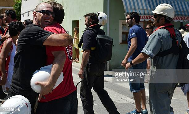 Salvage workers celebrate after the refloating operation of the Costa Concordia cruise liner on July 23 2014 in the island of Giglio Italy's...