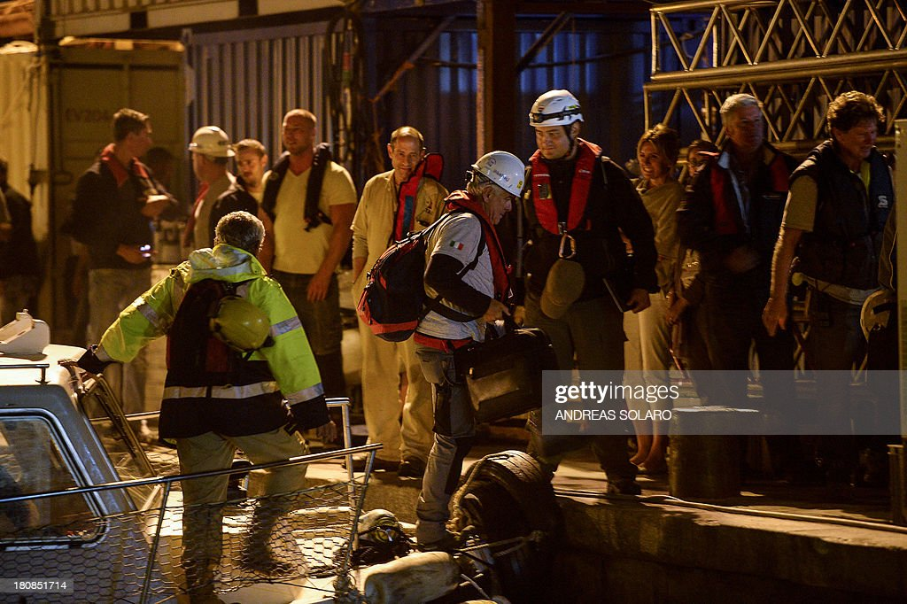 Salvage workers for Titan-Micoperi disembark a boat following the rotation of the wreck of Italy's Costa Concordia cruise ship on September 17, 2013 near the harbour of Giglio Porto. Salvage operators in Italy lifted the Costa Concordia cruise ship upright from its watery grave off the island of Giglio on September 17 in the biggest ever project of its kind.