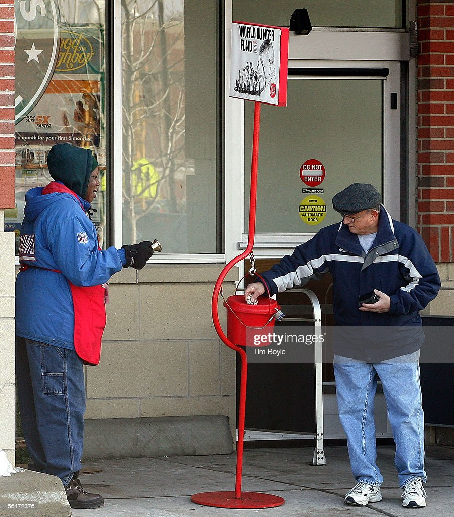 Salvation Army bell ringer Juanita Brown looks on as Joseph Dercher drops a donation into her red Holiday donation kettle December 20 2005 in Park...