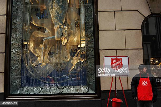 Salvation Army bell ringer stands in front of a holiday window display at Bergdorf Goodman on December 9 2013 in New York City With the lighting of...