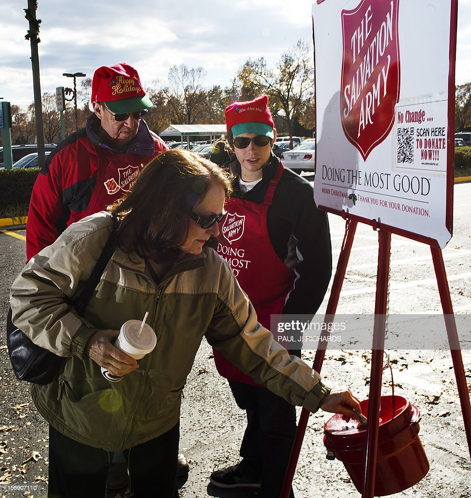 Salvation Army bell ringer volunteers William Schmidt (L), who is on his 20th year volunteering, and his grandson Bubba Wellens (R) look on as a women donates cash into the kettle outside a Giant grocery store November 24, 2012, in Clifton, Virgina. Salvation Army volunteers traditionally are seen collecting donations from holiday shopper for the needy between Thanksgiving and Christmas. AFP Photo/Paul J. Richards