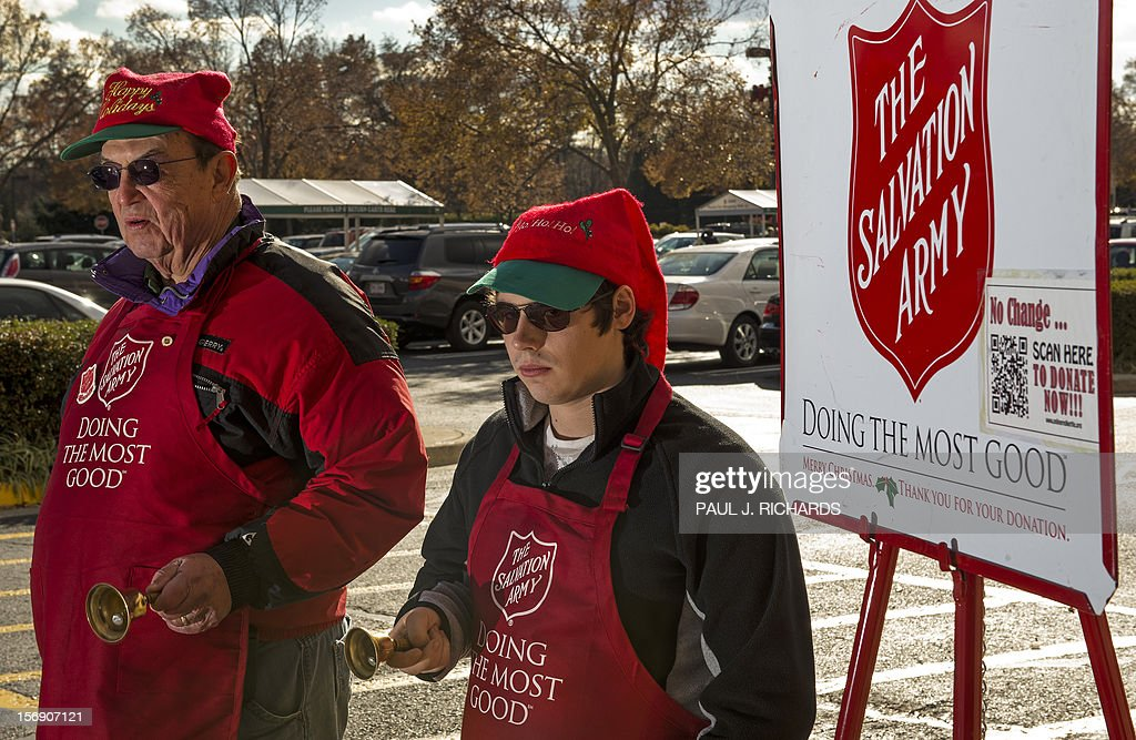 Salvation Army bell ringer volunteers William Schmidt(L), who is on his 20th year volunteering, and his grandson Bubba Wellens(R) ring their bells looking for a donation into a kettle outside a Giant grocery store November 24, 2012, in Clifton, Virgina. Salvation Army volunteers traditionally are seen collecting donations from holiday shopper for the needy between Thanksgiving and Christmas. Schmidt says he does it, ' to teach others the joy of giving. AFP Photo/Paul J. Richards