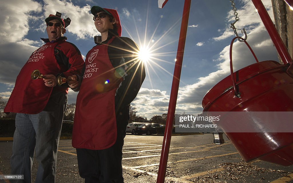 Salvation Army bell ringer volunteers William Schmidt who is on his 20th year volunteering and his grandson Bubba Wellens ring their bells looking...