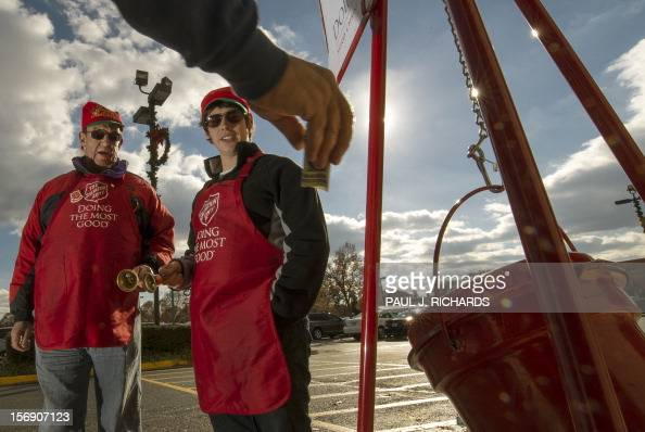 Salvation Army bell ringer volunteers William Schmidt who is on his 20th year volunteering and his grandson Bubba Wellens ring their bells thankfully...