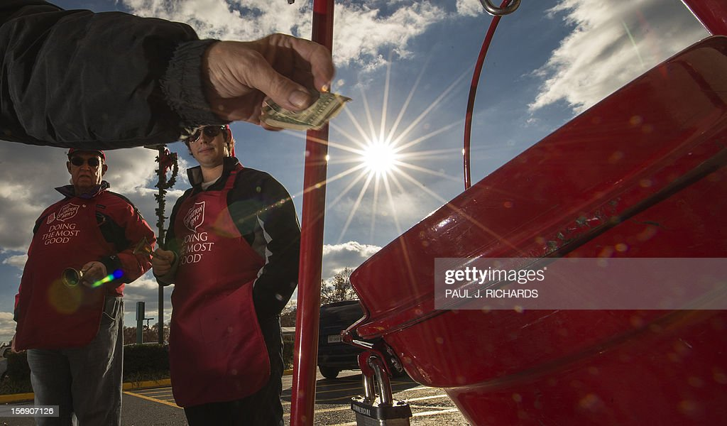 Salvation Army bell ringer volunteers William Schmidt (L), who is on his 20th year volunteering, and his grandson Bubba Wellens (R) ring their bells watching a donation into a kettle outside a Giant grocery store November 24, 2012, in Clifton, Virgina. Salvation Army volunteers traditionally are seen collecting donations from holiday shopper for the needy between Thanksgiving and Christmas. Schmidt says he does it, 'to teach others the joy of giving'. AFP Photo/Paul J. Richards