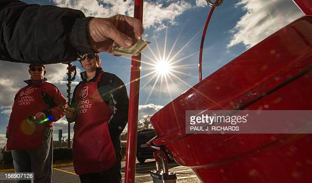 Salvation Army bell ringer volunteers William Schmidt who is on his 20th year volunteering and his grandson Bubba Wellens ring their bells watching a...