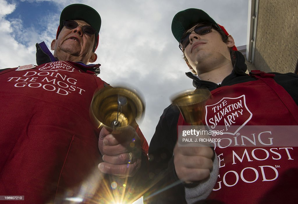 Salvation Army bell ringer volunteers William Schmidt (L), who is on his 20th year volunteering, and his grandson Bubba Wellens (R) ring their bells looking for a donation into a kettle outside a Giant grocery store November 24, 2012, in Clifton, Virgina. Salvation Army volunteers traditionally are seen collecting donations from holiday shopper for the needy between Thanksgiving and Christmas. Schmidt says he does it, ' to teach others the joy of giving. AFP Photo/Paul J. Richards