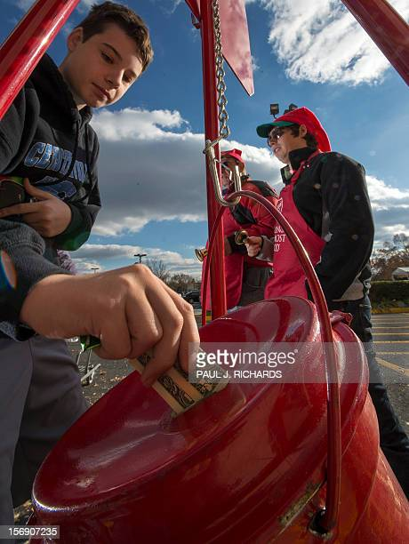 Salvation Army bell ringer volunteers William Schmidt who is on his 20th year volunteering and his grandson Bubba Wellens look as a donation is made...