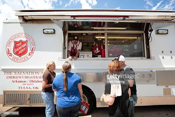 Salvation Army Cpt Jay Spalding and volunteer Mark Watson gives food to from left Christy Harper Hillary McKenzie and Judy and Frank Evanchyk May 23...
