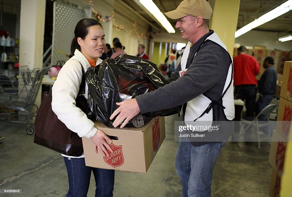 Salvation Army volunteer Randy Gilchrist helps a woman with a box a food and a bag of toys during a food and toy giveaway to families in need...