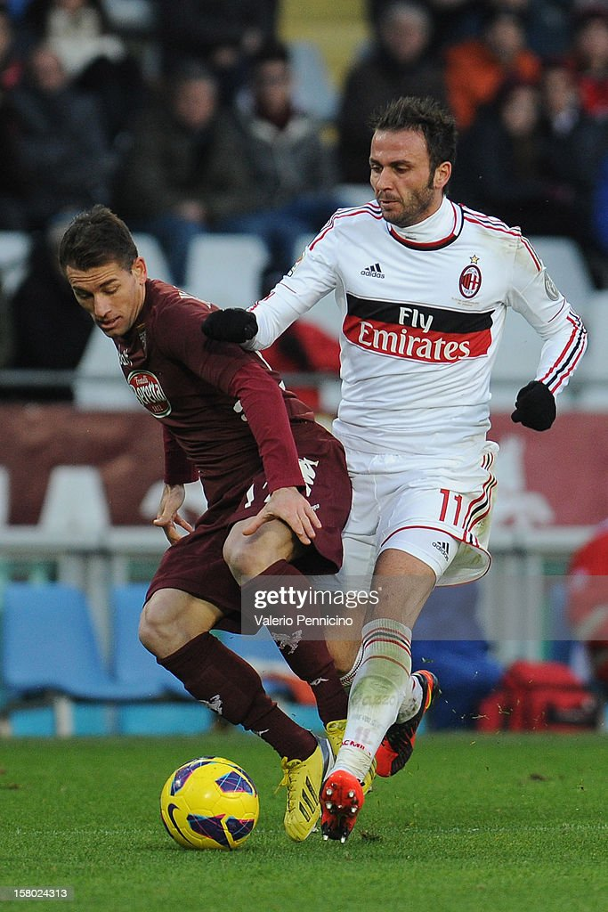 Salvatore Masiello (L) of Torino FC competes with <a gi-track='captionPersonalityLinkClicked' href=/galleries/search?phrase=Giampaolo+Pazzini&family=editorial&specificpeople=800179 ng-click='$event.stopPropagation()'>Giampaolo Pazzini</a> of AC Milan during the Serie A match between Torino FC and AC Milan at Stadio Olimpico di Torino on December 9, 2012 in Turin, Italy.