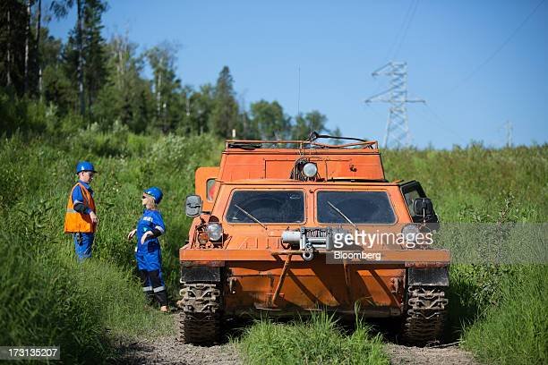 Salym Petroleum employees stand beside an offroad vehicle as they check underground oil pipelines in Salym KhantyMansi autonomous region Russia on...