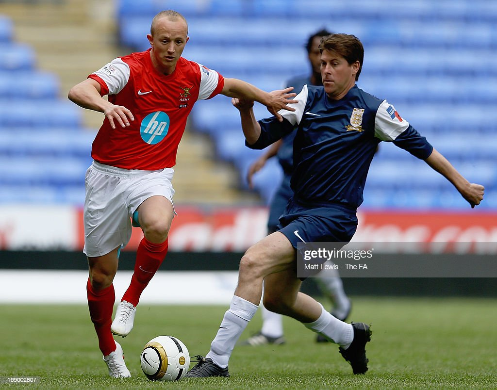 Sam Agar of the Army FA is tackled by <a gi-track='captionPersonalityLinkClicked' href=/galleries/search?phrase=Darren+Anderton&family=editorial&specificpeople=223907 ng-click='$event.stopPropagation()'>Darren Anderton</a> of the FA Legends during the Army FA and FA Legends Match at Madejski Stadium on May 18, 2013 in Reading, England.