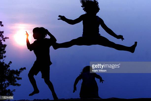 Sam Anne and Kyndra Hendrick have some fun jumping on a trampoline while the sun sets in the background June 21 2001 in Lower Marlboro Maryland