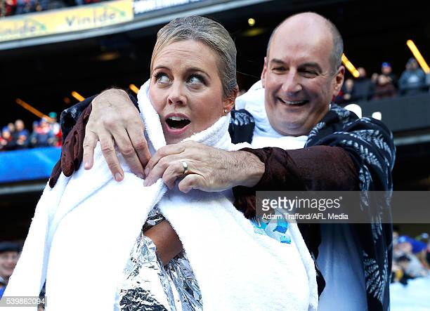 Sam Armytage is handed a towel by David Koch after going down the Freeze MND slide during the Big Freeze 2 during the 2016 AFL Round 12 match between...