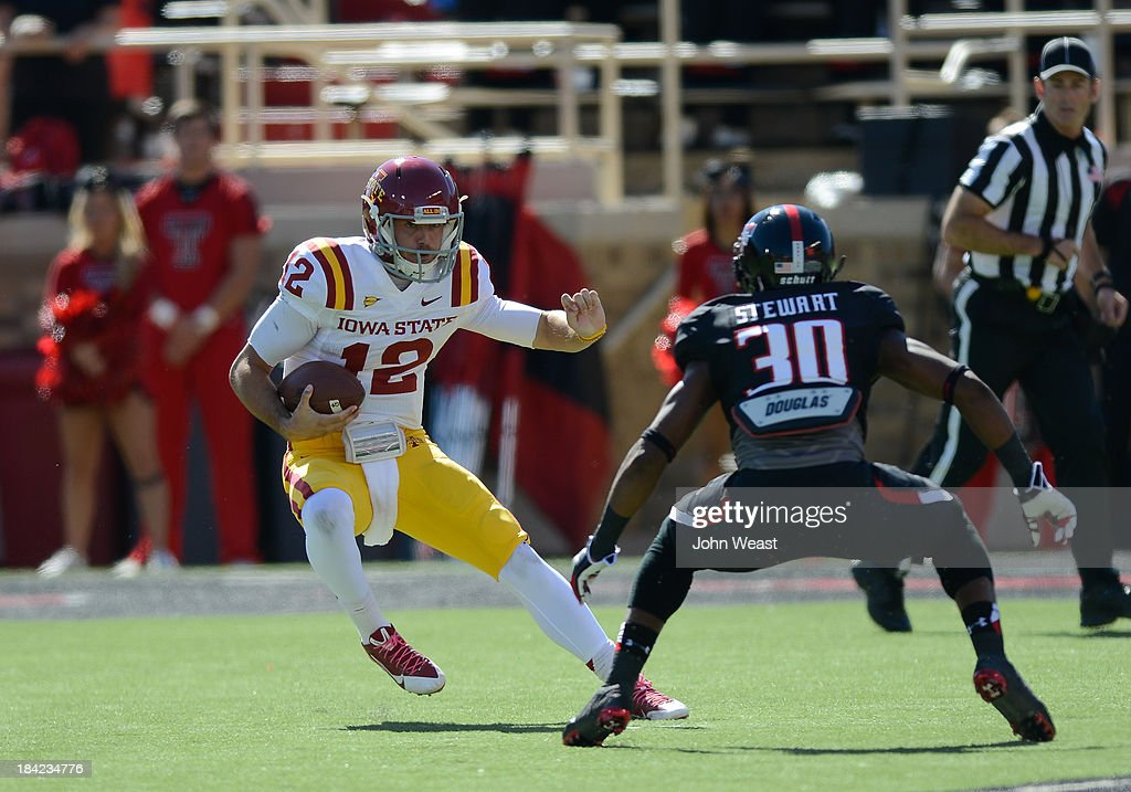 Sam B. Richardson #12 of the Iowa State Cyclones ttys to get by Austin Stewart #30 of the Texas Tech Red Raiders during game action on October 12, 2013 at AT&T Jones Stadium in Lubbock, Texas. Texas Tech won the game over Iowa State 42-35.