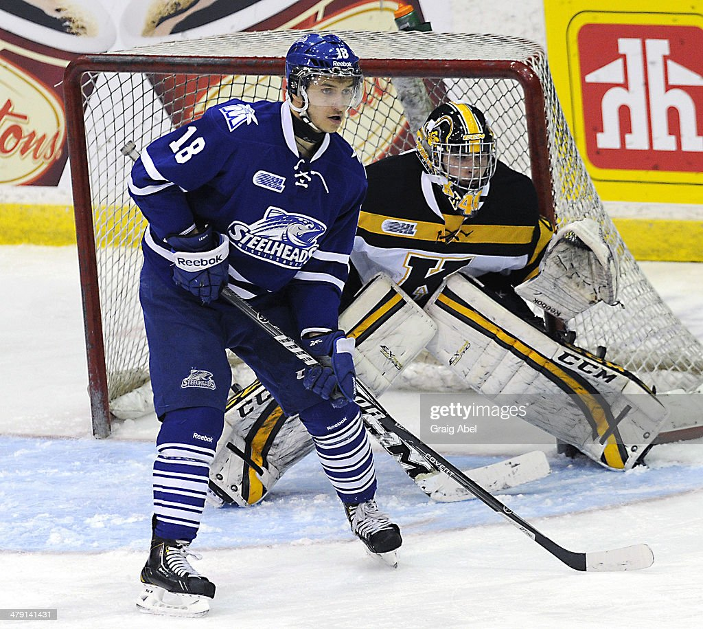 Sam Babintsev #18 of the Mississauga Steelheads screens goalie Lucas Peressini #40 of the Kingston Frontenacs during game action on March 16, 2014 at the Hershey Centre in Mississauga, Ontario, Canada.
