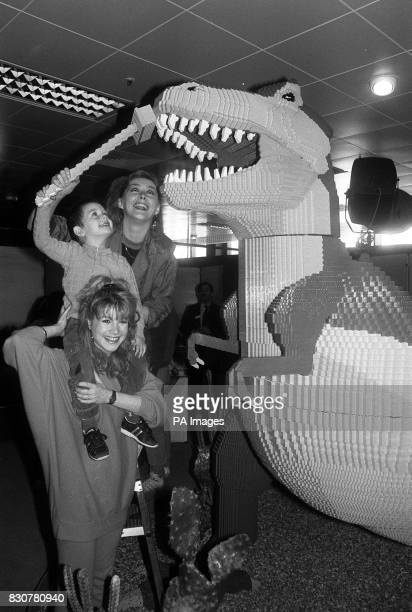 Sam Baker aged 3 gets the chance to clean the teeth of a Lego TRex with the help of Bucks Fizz singers Shelley Preston and Cheryl Baker in Debenhams...
