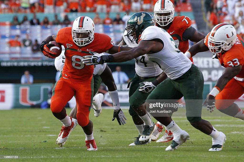 Sam Barrington #36 of the South Florida Bulls attempts to tackle Duke Johnson #8 of the Miami Hurricanes as he runs with the ball on November 17, 2012 at Sun Life Stadium in Miami Gardens, Florida. The Hurricanes defeated the Bulls 40-9.