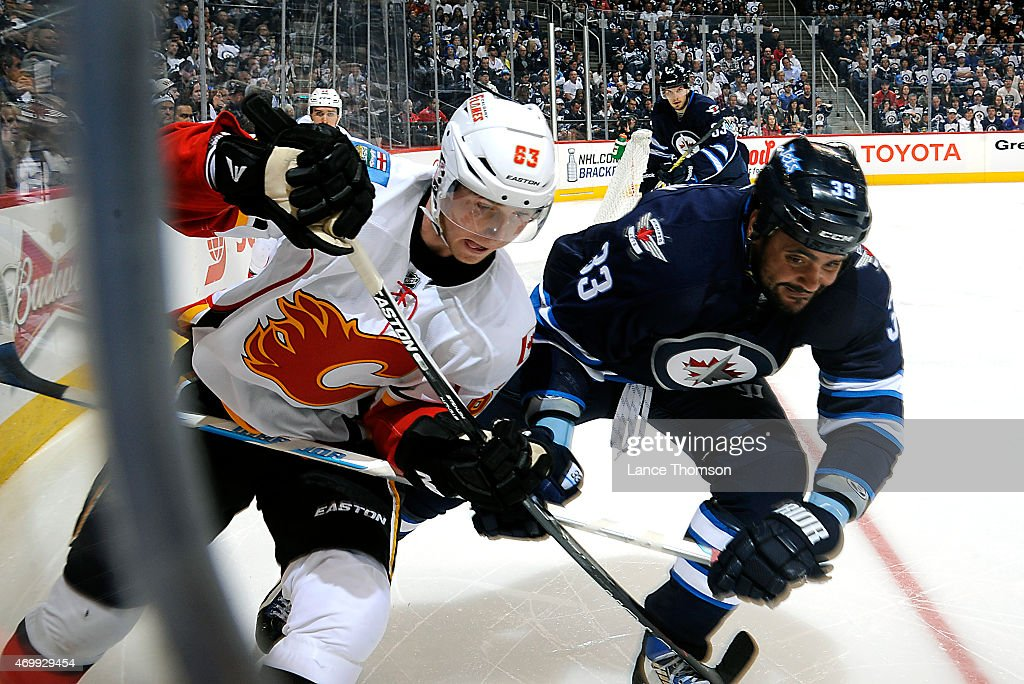 Sam Bennett of the Calgary Flames and Dustin Byfuglien of the Winnipeg Jets battle along the corner boards as they chase the puck during third period...