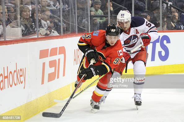 Sam Bennett of the Calgary Flames and Mark Scheifele of the Winnipeg Jets follow the play around the boards during third period action at the MTS...