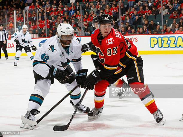 Sam Bennett of the Calgary Flames battles against Joel Ward of the San Jose Sharks at Scotiabank Saddledome on March 7 2016 in Calgary Alberta Canada