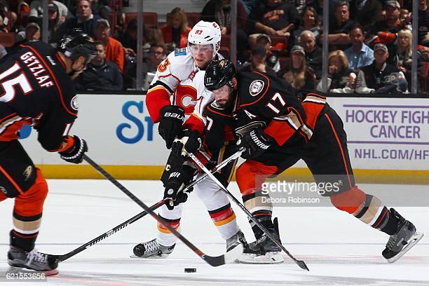 Sam Bennett of the Calgary Flames battles for the puck against Ryan Kesler and Ryan Getzlaf of the Anaheim Ducks on November 6 2016 at Honda Center...