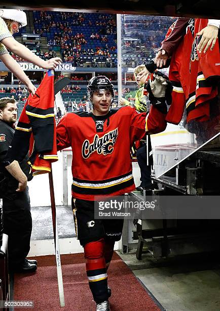 Sam Bennett of the Calgary Flames exhanges highfives with fans before an NHL game against the Winnipeg Jets at Scotiabank Saddledome on December 22...