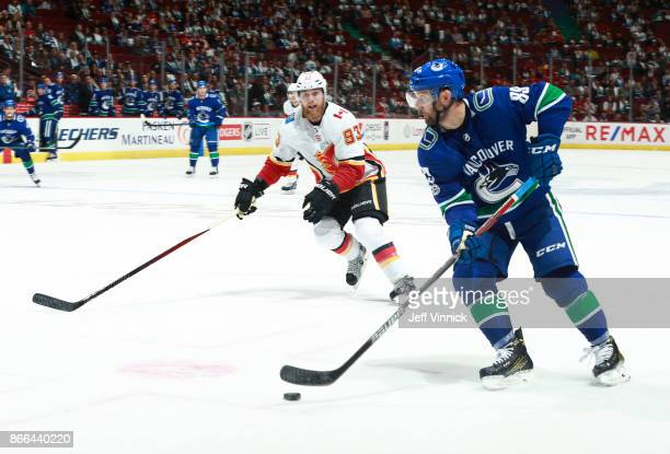 Sam Bennett of the Calgary Flames looks on as Sam Gagner of the Vancouver Canucks skates up ice with the puck during their NHL game at Rogers Arena...