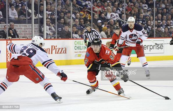 Sam Bennett of the Calgary Flames plays the puck down the ice as Toby Enstrom of the Winnipeg Jets defends during third period action at the MTS...