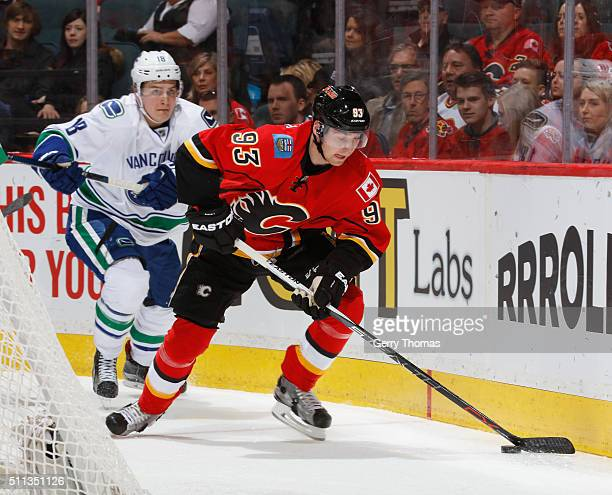Sam Bennett of the Calgary Flames protects the puck against Jake Virtanen of the Vancouver Canucks at Scotiabank Saddledome on February 19 2016 in...