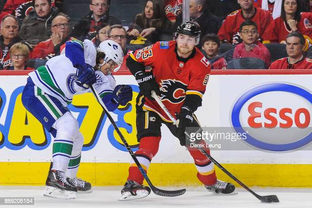 Sam Bennett of the Calgary Flames skates with the puck past Loui Eriksson of the Vancouver Canucks during an NHL game at Scotiabank Saddledome on...