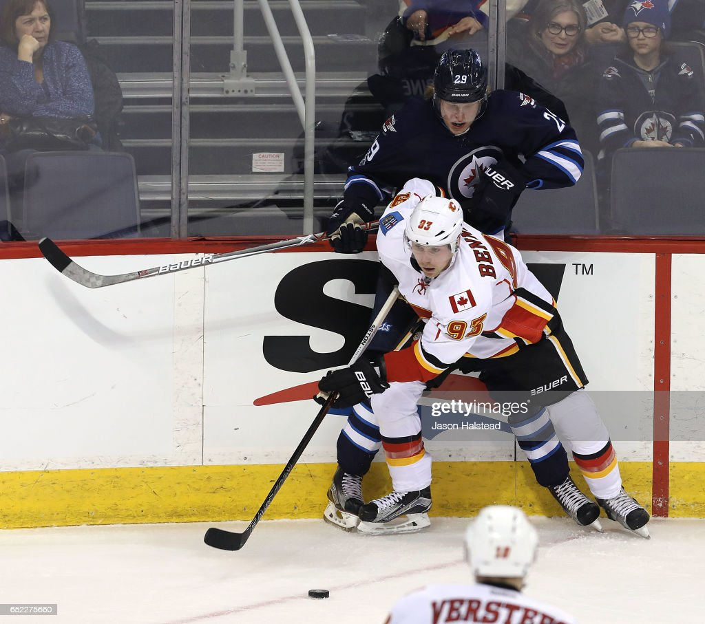 Sam Bennett #93 of the Calgary Flames takes the puck from Patrik Laine #29 of the Winnipeg Jets during NHL action on March 11, 2017 at the MTS Centre in Winnipeg, Manitoba.