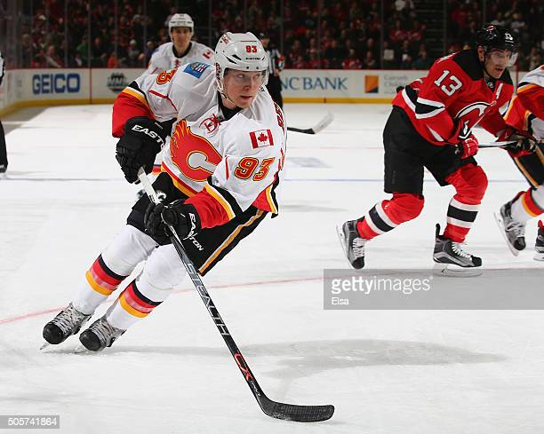 Sam Bennett of the Calgary Flames takes the puck in the third period as Michael Cammalleri of the New Jersey Devils defends on January 192016 at...
