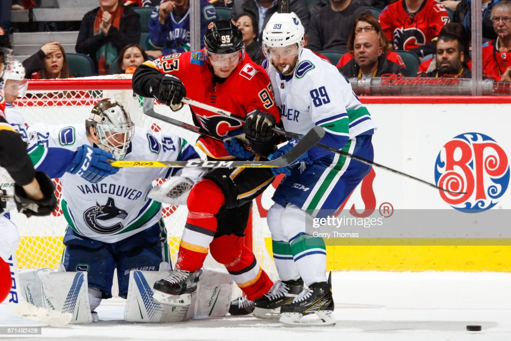 Sam Bennett #93 of the Calgary Flames tries to deflect a shoot while guarded by Sam Gagner #89 in an NHL game against the Vancouver Canucks at the Scotiabank Saddledome on November 7, 2017 in Calgary, Alberta, Canada.