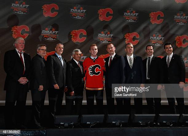 Sam Bennett poses on stage with President of Hockey Operations Brian Burke General Manager Brad Treliving Assistant General Manager Craig Conroy...