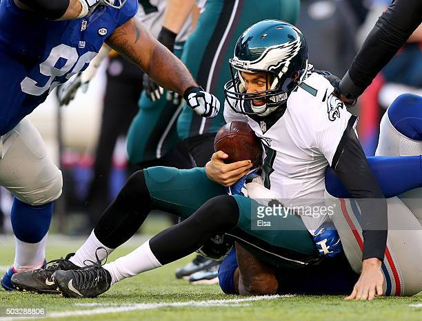 Sam Bradford of the Philadelphia Eagles is sacked by Robert Ayers of the New York Giants at MetLife Stadium on January 3 2016 in East Rutherford New...