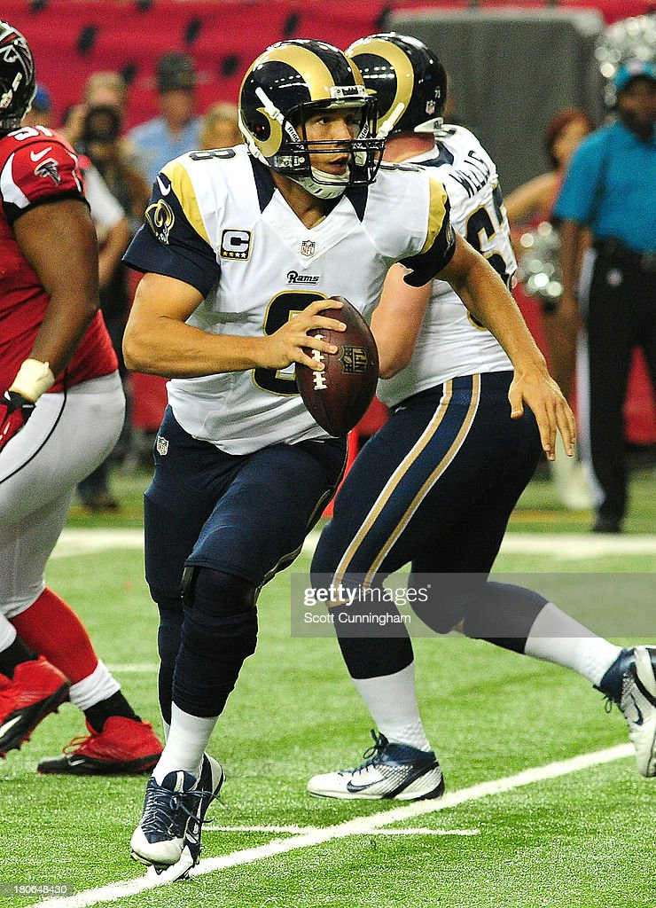 Sam Bradford #8 of the St. Louis Rams rolls out to pass against the Atlanta Falcons at the Georgia Dome on September 15, 2013 in Atlanta, Georgia.