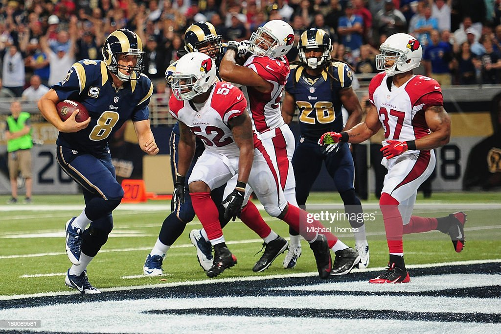 <a gi-track='captionPersonalityLinkClicked' href=/galleries/search?phrase=Sam+Bradford&family=editorial&specificpeople=4489292 ng-click='$event.stopPropagation()'>Sam Bradford</a> #8 of the St. Louis Rams scores on a two-point conversion against <a gi-track='captionPersonalityLinkClicked' href=/galleries/search?phrase=Jasper+Brinkley&family=editorial&specificpeople=4032417 ng-click='$event.stopPropagation()'>Jasper Brinkley</a> #52 of the Arizona Cardinals at the Edward Jones Dome on September 8, 2013 in St. Louis, Missouri.