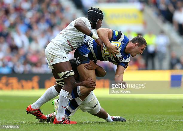 Sam Burgess of Bath is tackled by Maro Itoje of Saracens and Mako Vunipola of Saracens during the Aviva Premiership Final between Bath Rugby and...