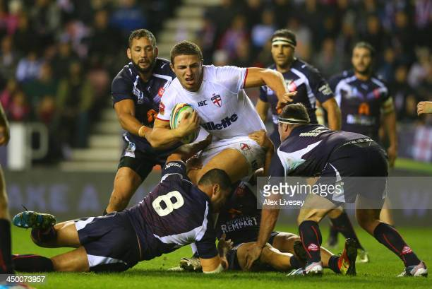 Sam Burgess of England holds off a challenge from Jamal Fakir and Remi Casty of France during the Rugby League World Cup Quarter Final match between...