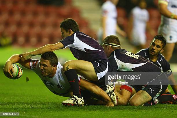 Sam Burgess of England is pulled up just short of the try line by Morgan Escare and Remi Casty of France during the Rugby League World Cup Quarter...