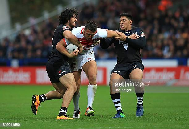 Sam Burgess of England is tackled by Tohu Harris and Jason Taumalolo New Zealand during the Four Nations match between England and New Zealand Kiwis...